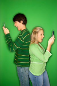 Caucasian teen boy and girl on cellphones.
