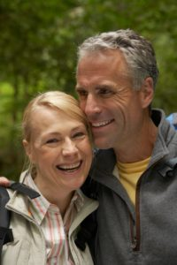 Mature man and woman embracing in forest, smiling