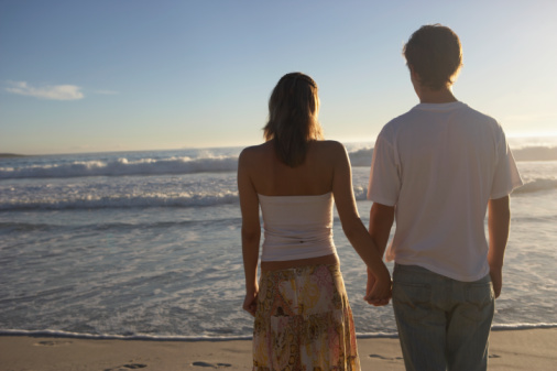 Teenage boy (14-16) and young woman holding hands on beach, rear view
