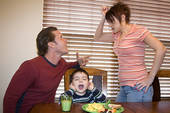 parents yelling at dinner table with little boy with his fingers in his ears